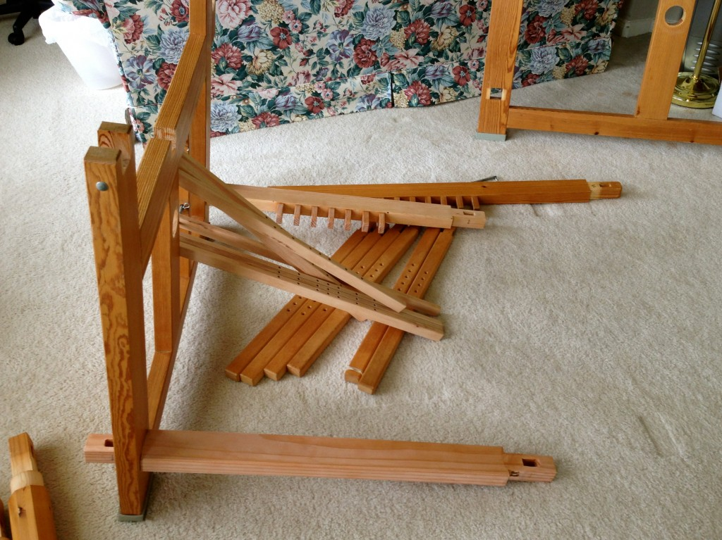 New pieces for 70cm loom being added: treadle beam at the back, foot rest at the front, and upper and lower lamms in the middle. No need to replace the treadles, on the floor by the old 100cm treadle beam.
