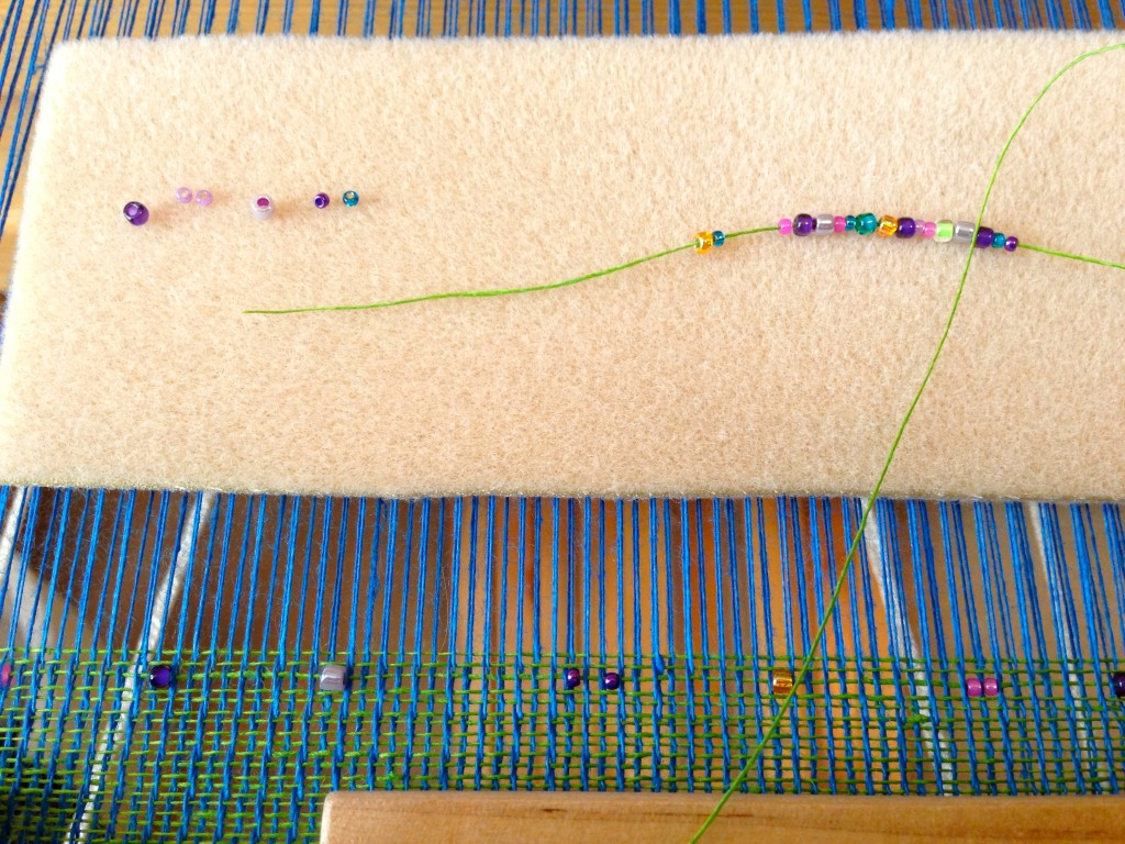 Adding beads to a linen thread for weaving.