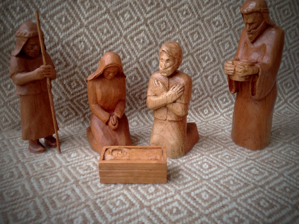 Hand-carved Nativity from Spanish Cedar, backdrop of handwoven goose-eye throw.