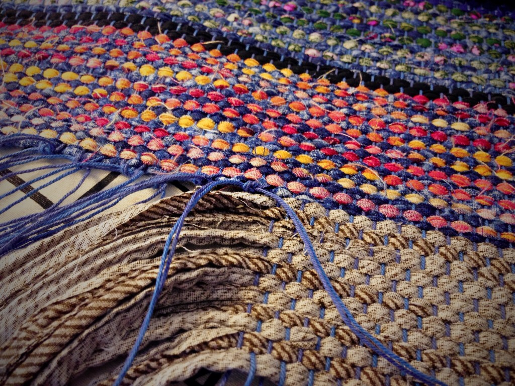 Securing rag rug hem with square knots.