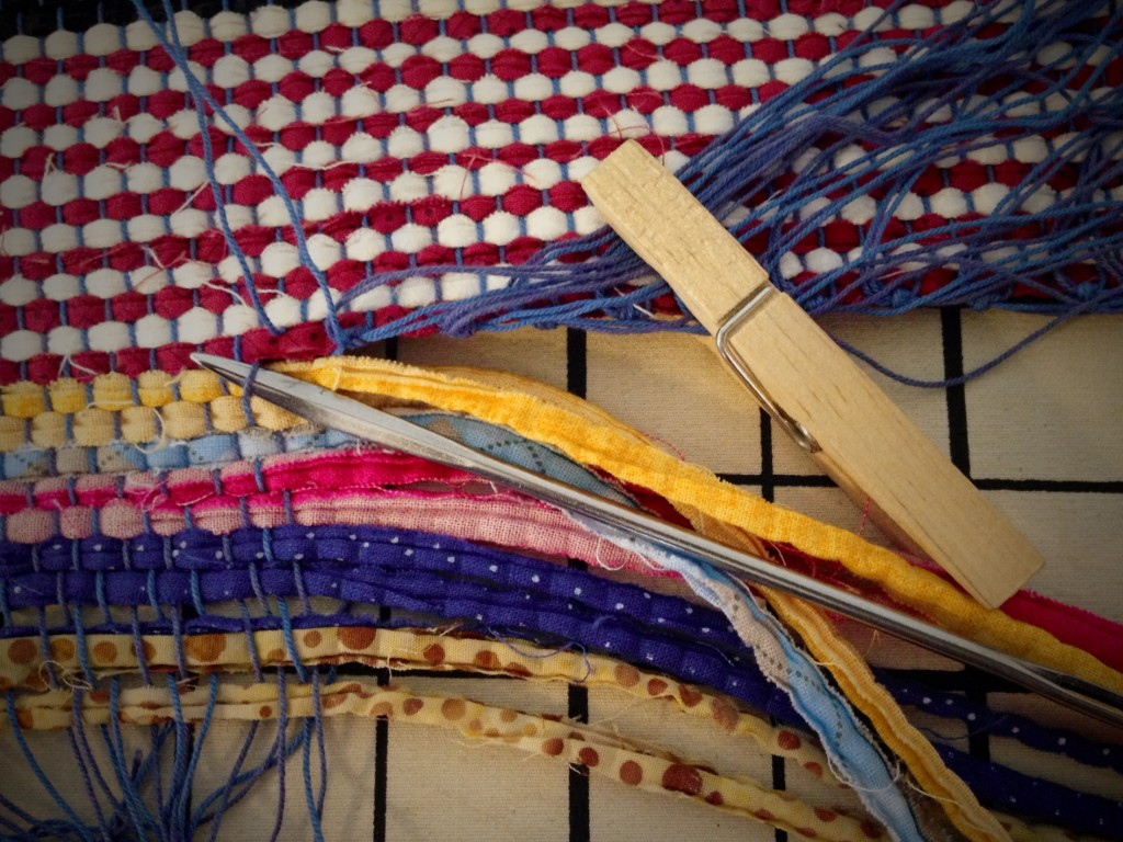 Upholstery needle helps separate warp ends from header to secure ends of rag rug.