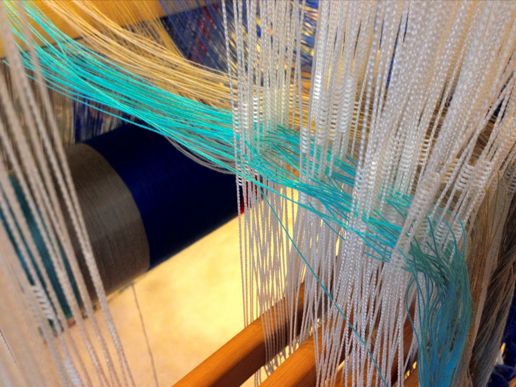 Threading Texsolv heddles for cotton hand towels.