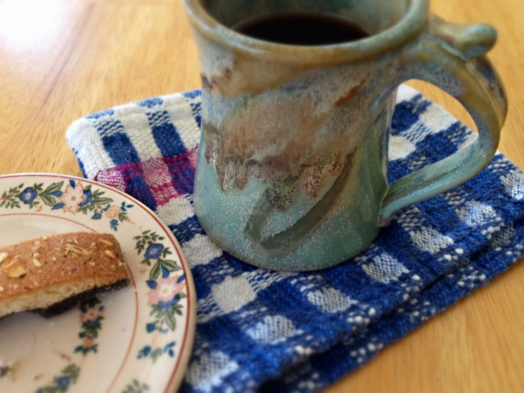 Handwoven scrap is used as a napkin/coaster for cup of coffee.