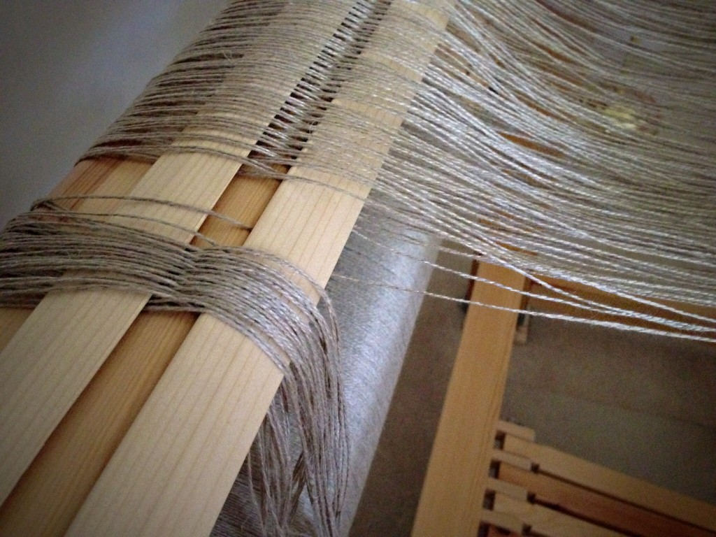 Threading 8/2 linen warp. Lease sticks show which thread is next.