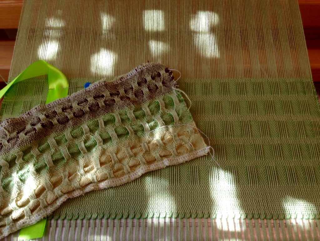 Wet finished sample compared with lace weave scarf on the loom.