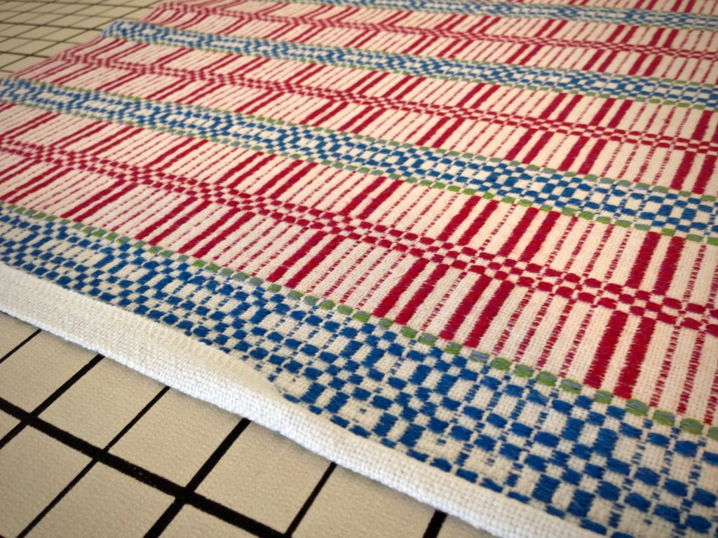 Folding edge under for hemming. Handwoven table squares.