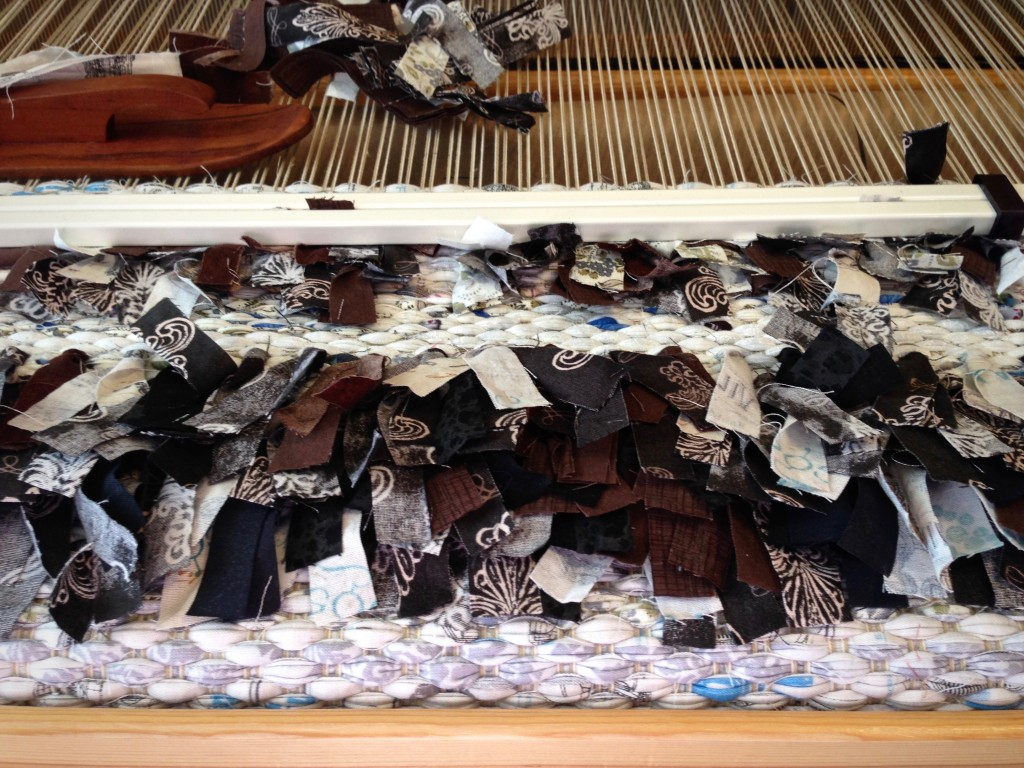 Placing rya knots in large rag rug.