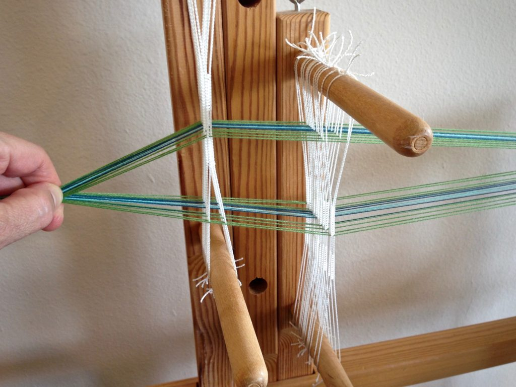 Warping the band loom.