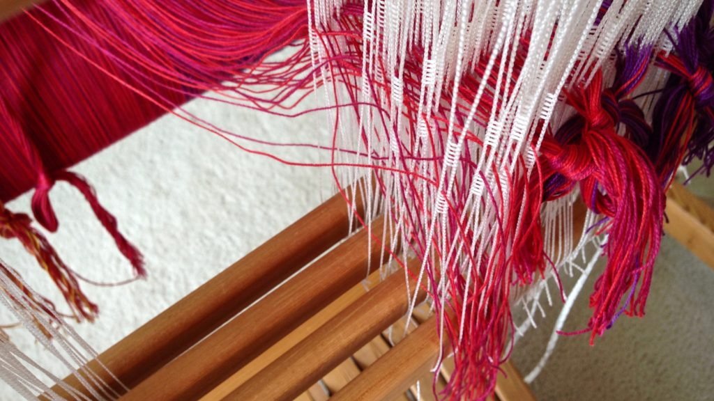 Threading cotton warp for woven baby wrap.