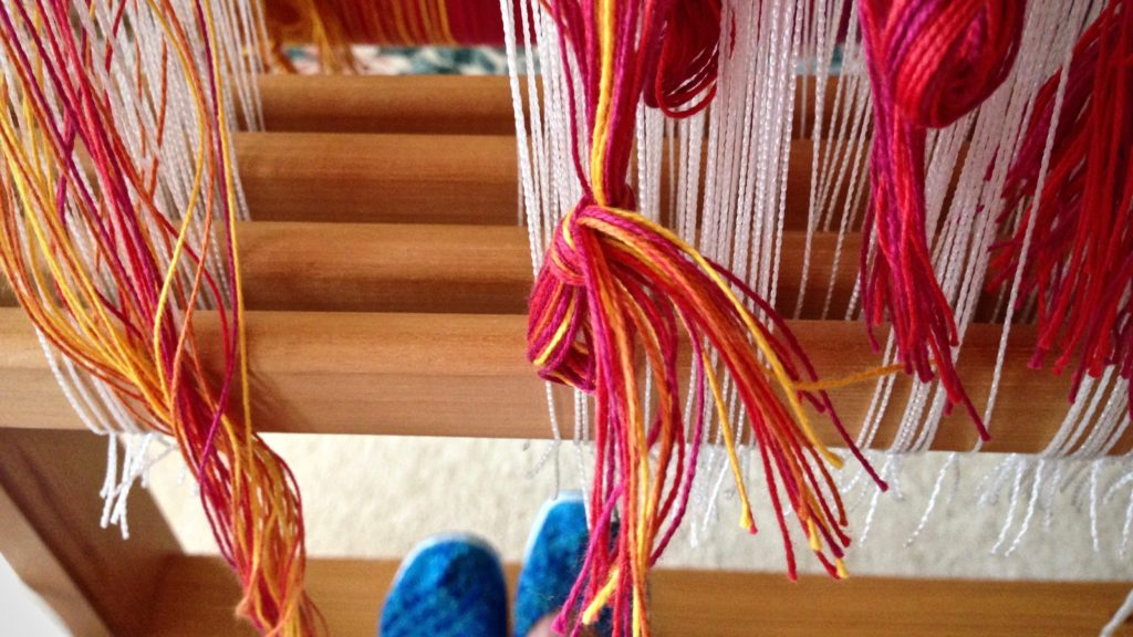 Threading brightly-colored warp for handwoven baby wrap.