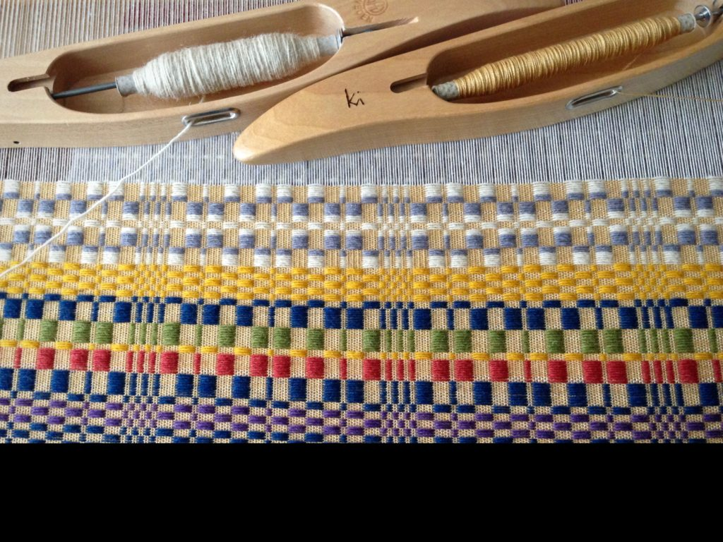 Swedish overshot, such as monksbelt, uses two shuttles--one for fine thread, and one for the thicker pattern weft. Warp is 16/2 cotton. Ground weave weft is 16/2 cotton. Pattern weft is 61 Fårö wool. Sett is 22 1/2 ends per inch. Weft density is 30 pattern picks per inch, with 2 tabby picks in between.