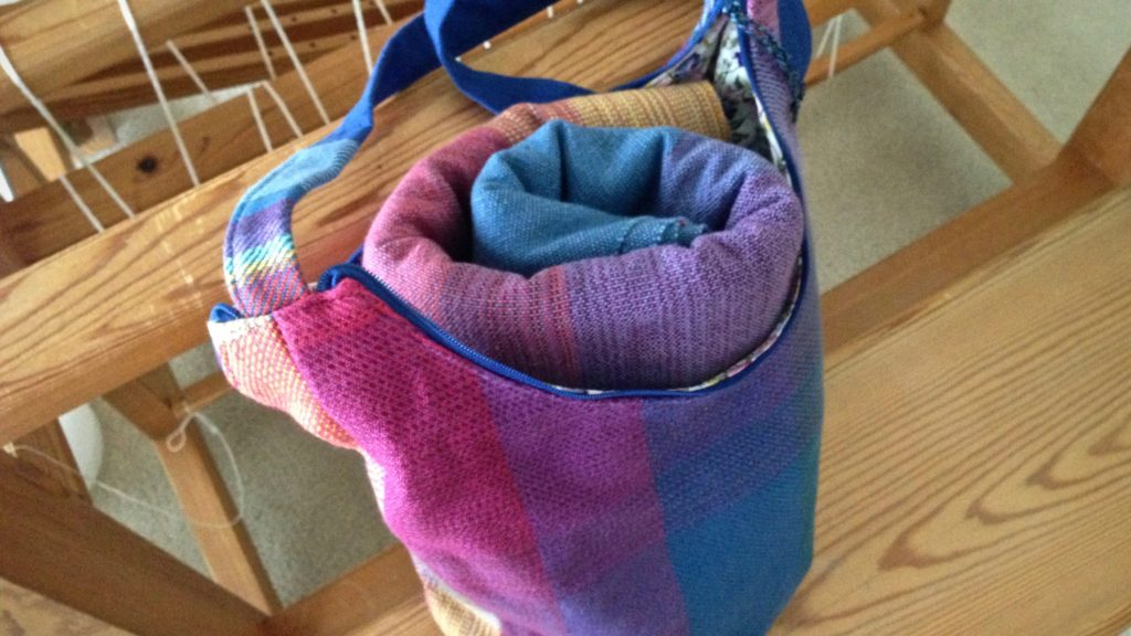 Finished handwoven handbag holds rolled baby wrap. Karen Isenhower