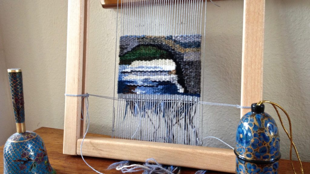 Bridge takes shape in small tapestry.