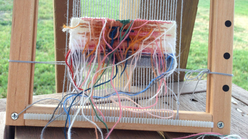 Weaving from the back on small travel tapestry frame loom.