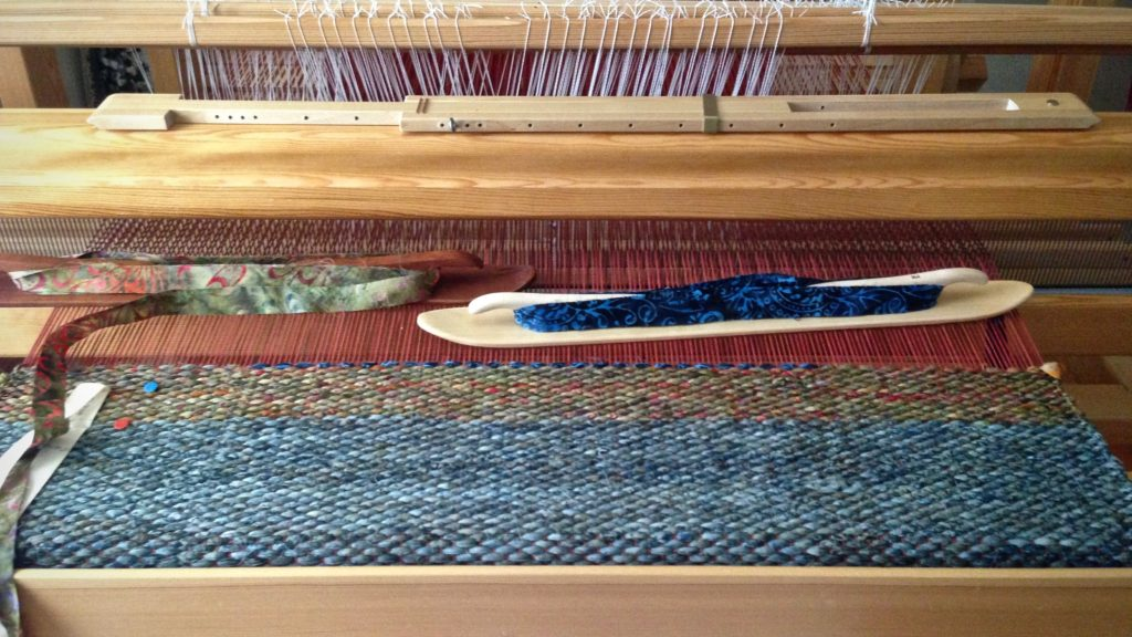 Double binding rag rug being woven with two ski shuttles.