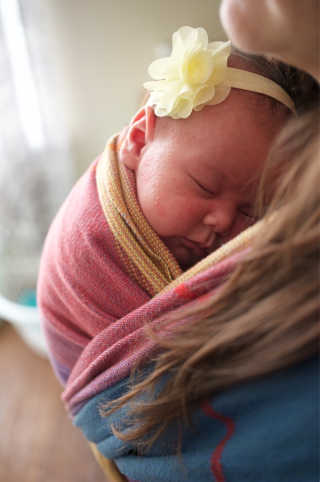 Handwoven baby wrap holding new baby.