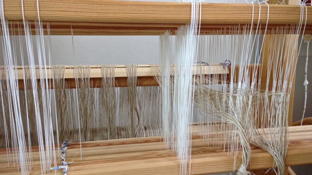 Threading heddles on eight shafts.
