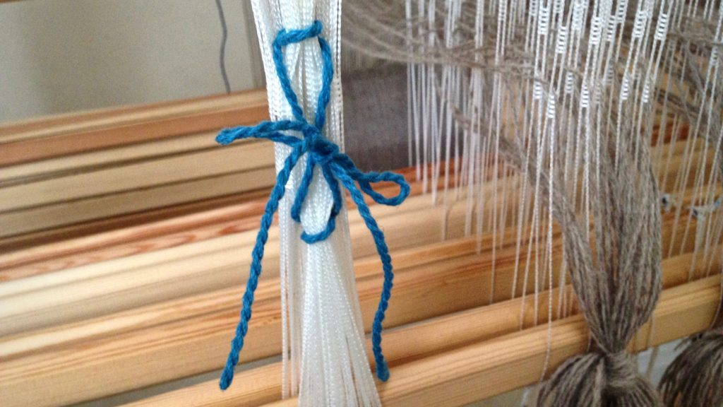 Removing Texsolv heddles after threading is complete.