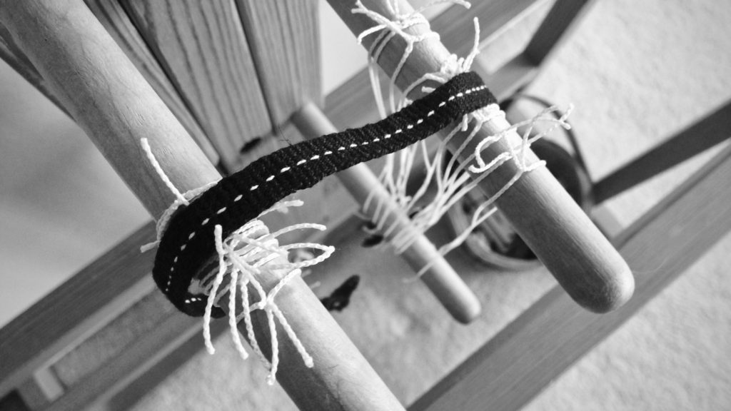 Black woven band with dotted white line. Glimakra band loom.