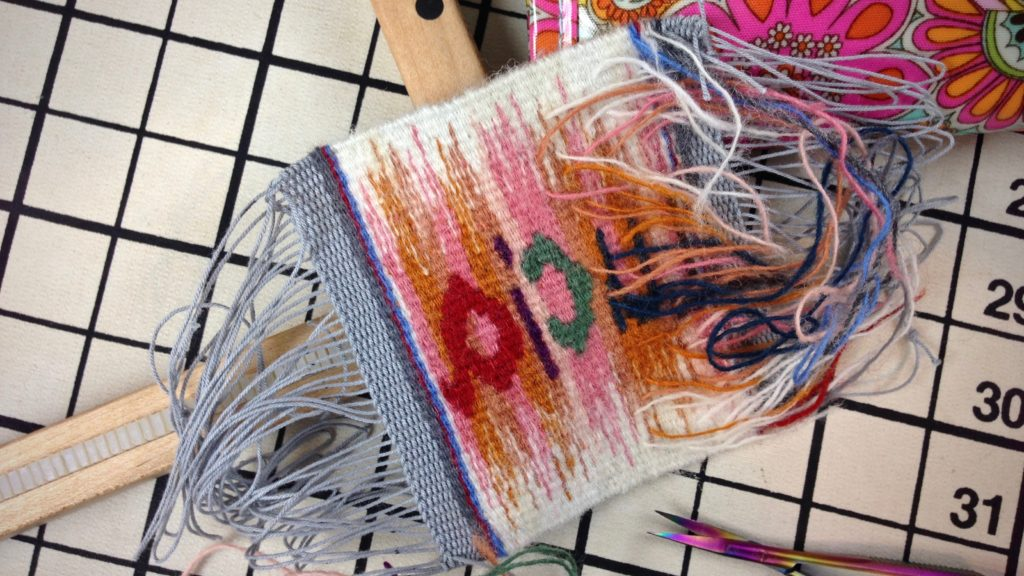 Back of small tapestry, stitching in weft tails.