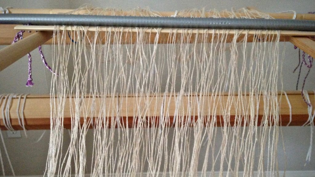 Dressing the loom with a linen warp.