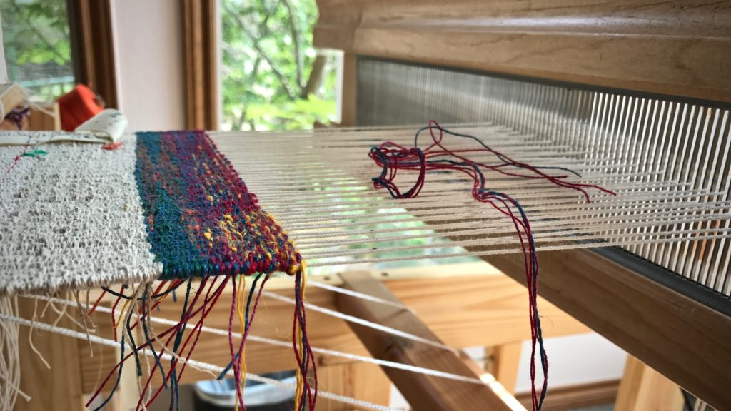 Windows beside the little loom light up the linen tapestry sampler.