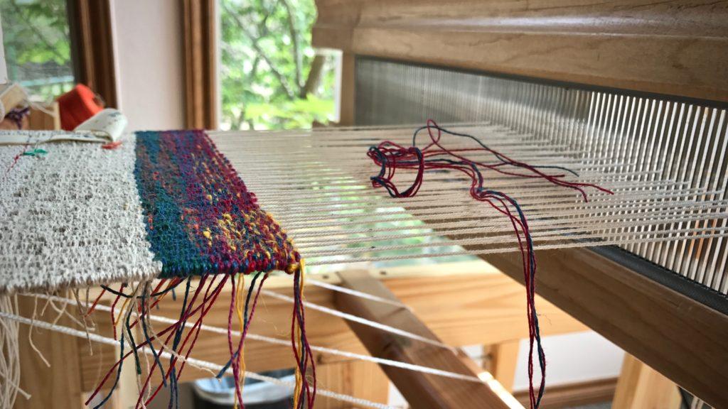 Windows beside the little loom light up the linen tapestry sampler.