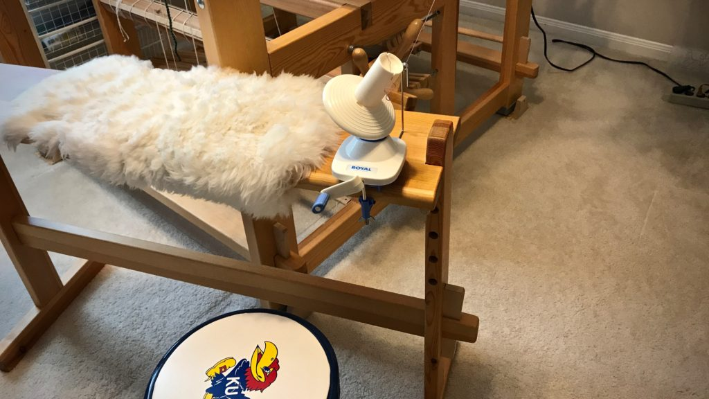 Yarn ball winder in use with umbrella swift.