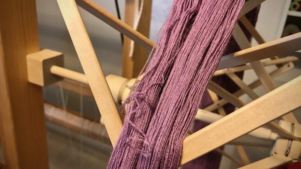 Putting skein of yarn on umbrella swift.