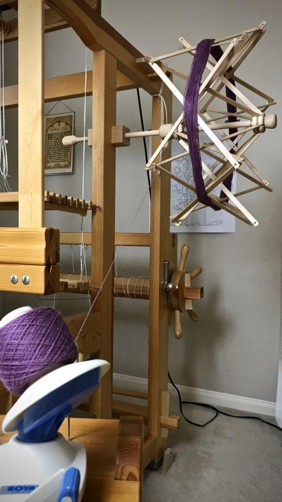 Winding ball of yarn from umbrella swift.