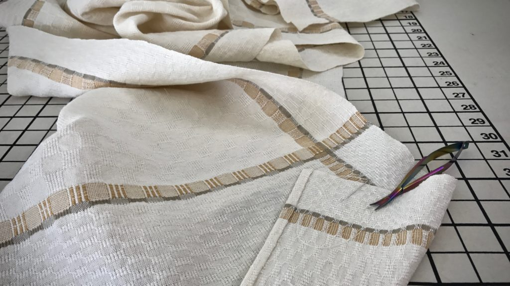 Long M's and O's table runner is hemmed by hand.