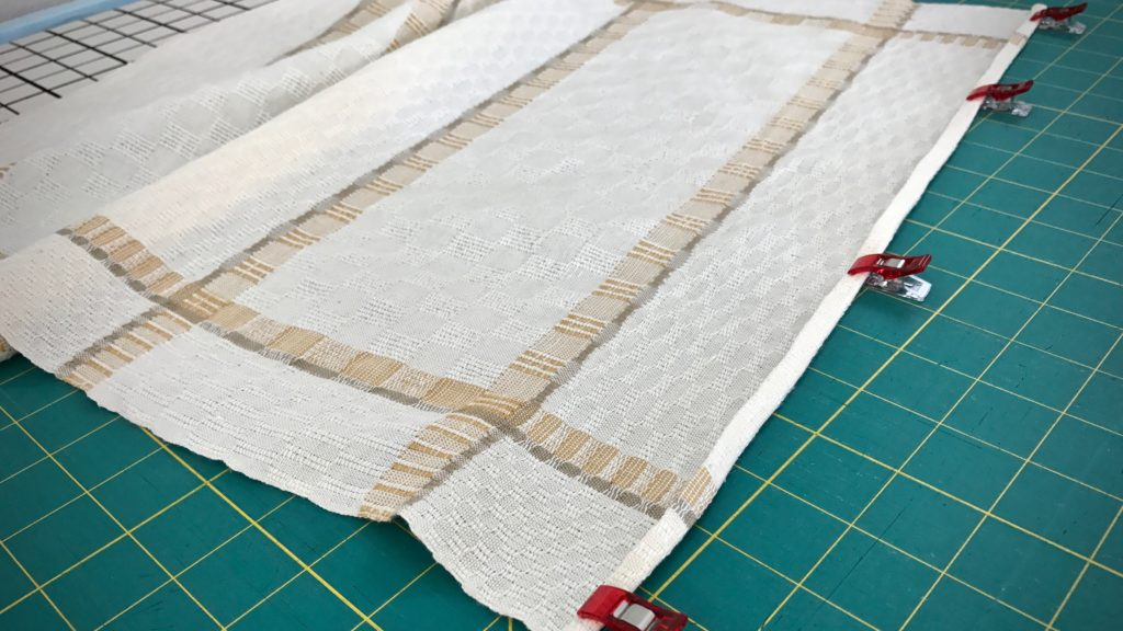 Sewing narrow hems on handwoven towels.