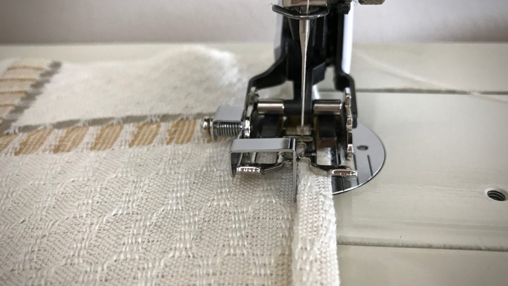 Sewing hems on handwoven towels.