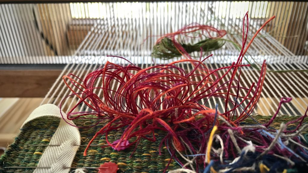Making rya knots with a bundle of linen threads.