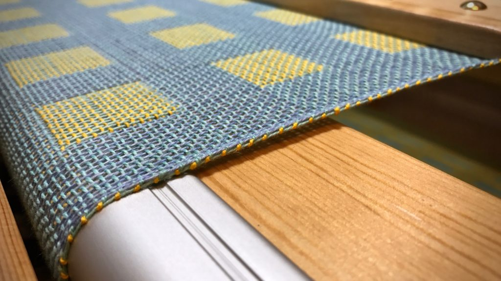 Sunshine yellow weft thread decorates the selvedge.
