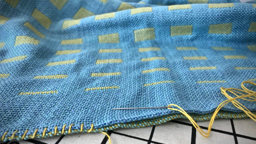 Embroidered edge of handwoven baby blanket.