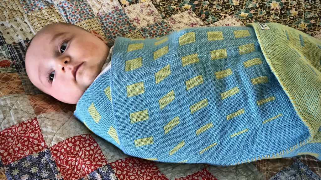 Handwoven baby blanket. (Resting on his great-great-grandmother's quilt.)
