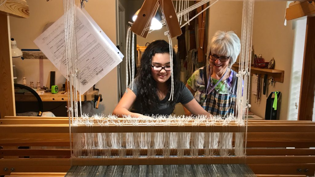 Young apprentice. First time at the loom.