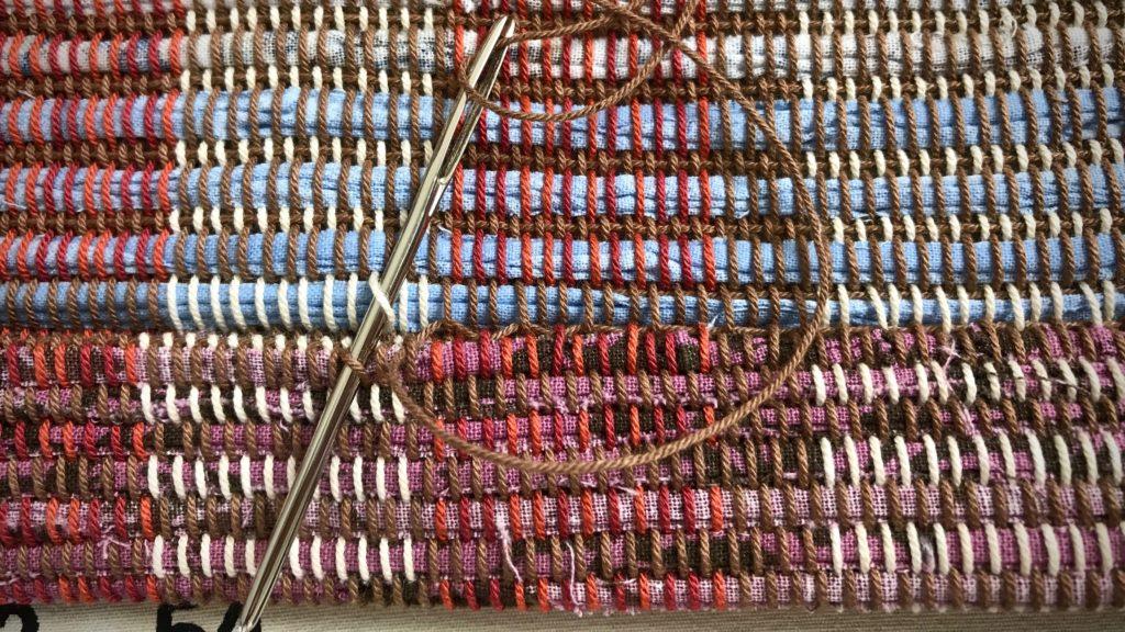 Hemming a handwoven rag rug.