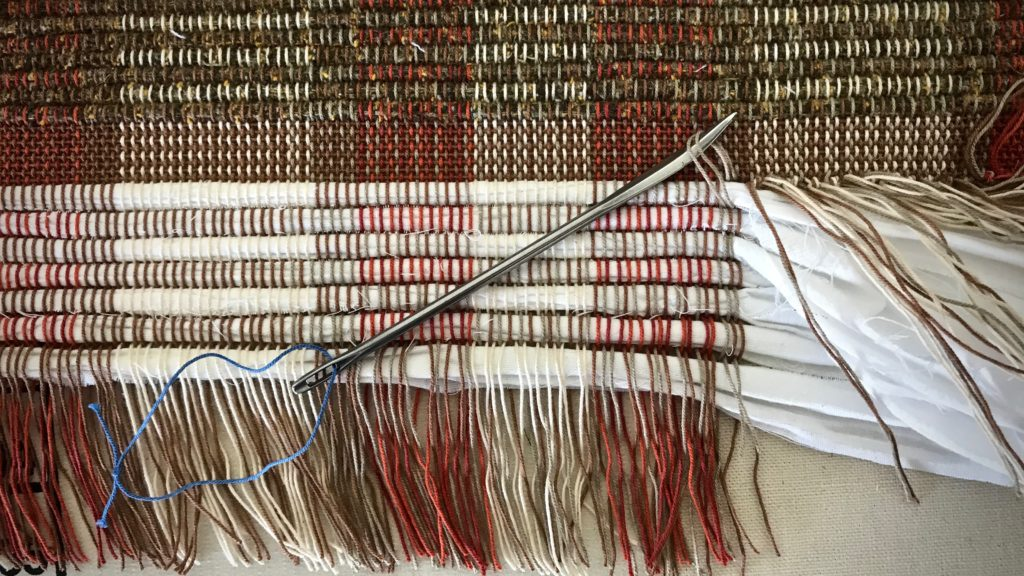 Tying warp ends into knots. Rag rug finishing.
