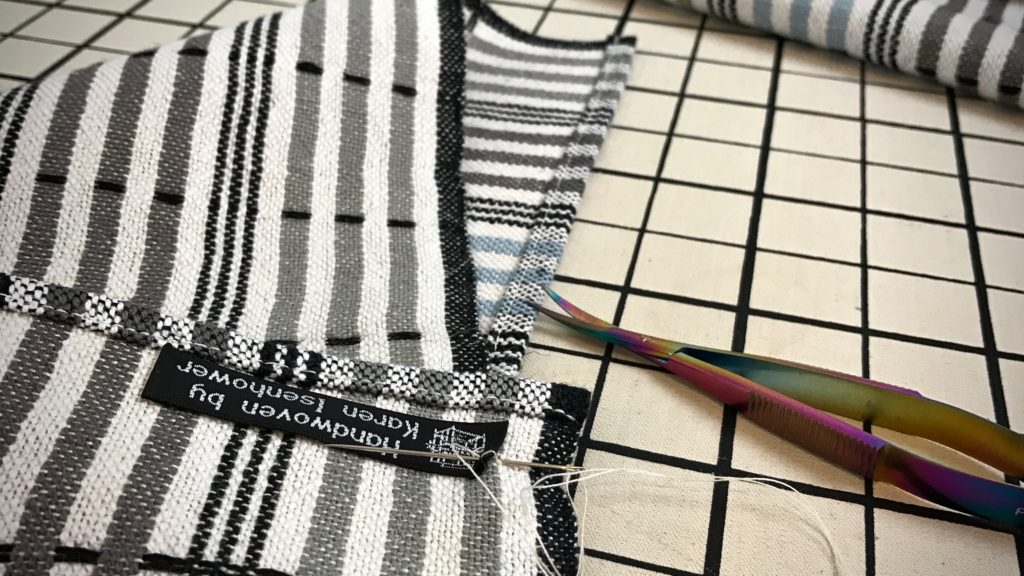 Stitching labels onto handwoven towels.