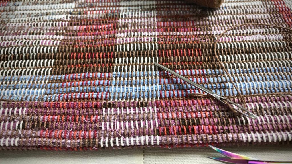 Rag rug hemming by hand.
