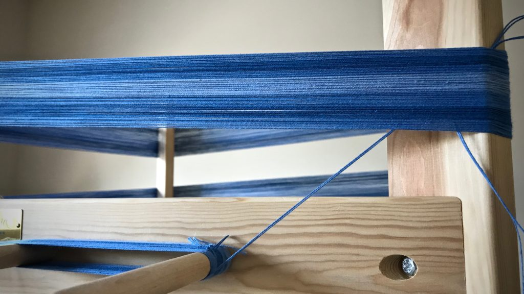 Winding a warp on a warping reel.