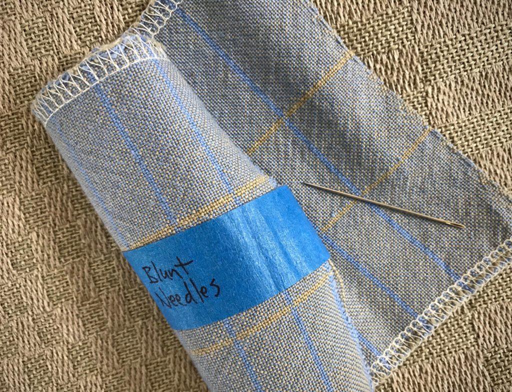 Blunt needle for fixing weaving errors.