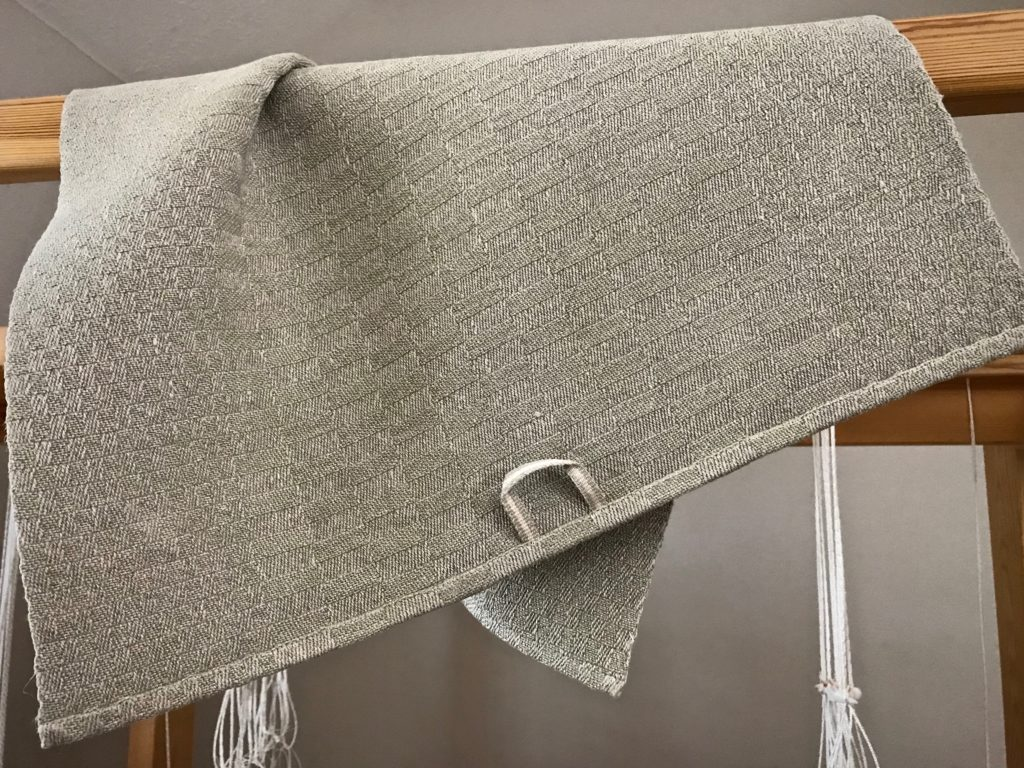 Handwoven linen towel with handwoven hanging tab.
