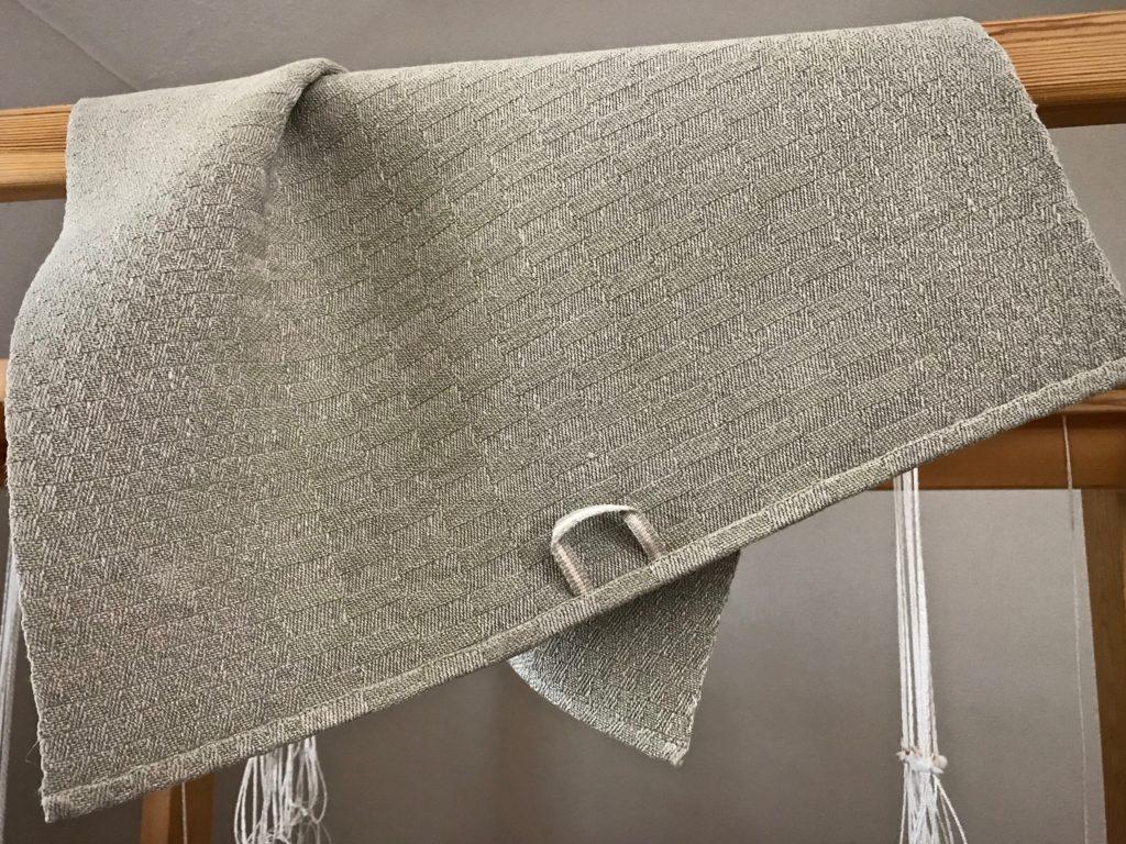 Handwoven linen towel with handwoven hanging tab.
