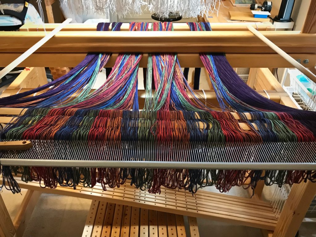 Pre-sleying the reed at the loom.