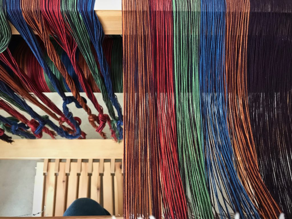 "Threading heddles in my ""playhouse"" in the loom."