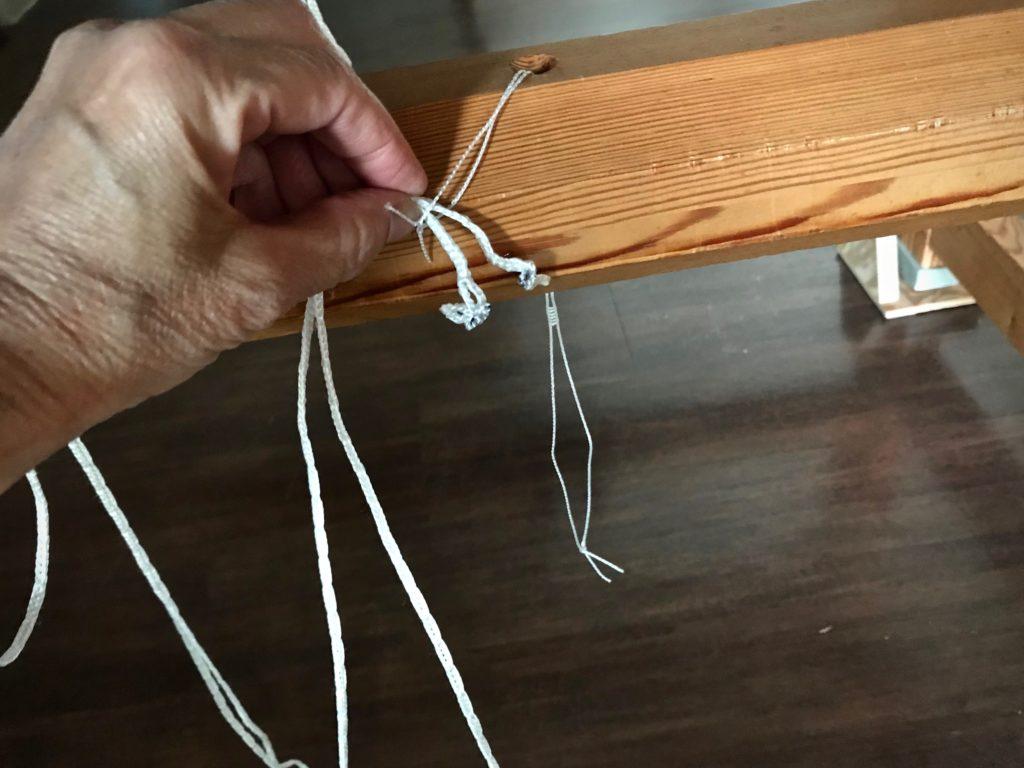 Using a spare heddle as a cord threader.
