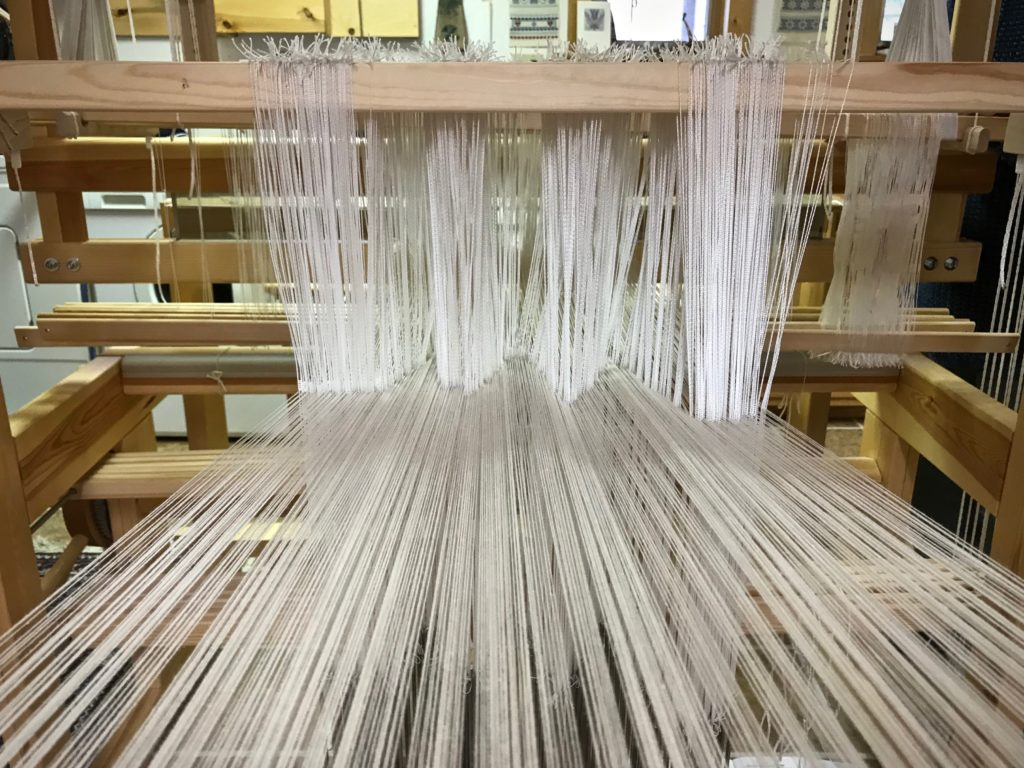 Pointed threading of pattern heddles on the drawloom.